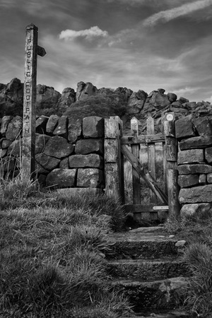 atmospheric: an atmospheric and mysterious black and white image of an old wooden gate with a signpost showing a public right of way footpath Stock Photo