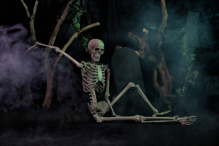lit image: A humorous image of a skeleton resting on a gravestone spookily lit and with mist smoke