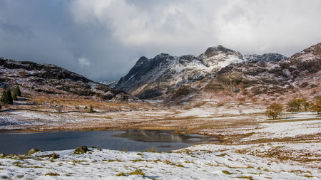 langdale pikes: Wintery scene taken at Blea Tarn in Cumbria on the Little Langdale to Great Langdale road. It has a backdrop of the Langdale Pikes Stock Photo