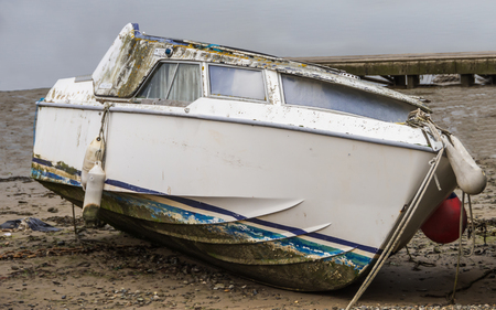 beached: An old derelict boat beached on the sand and named lets party Stock Photo