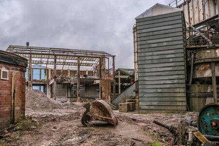 dismantle: A demolition site of an old factory with rubble and steelwork with a bucket from an excavator  in the foreground and no machinery Editorial