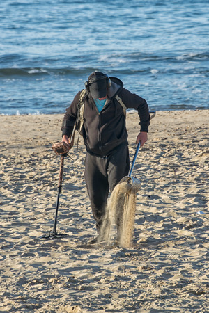 A metal detector searching in the sand on a beach with the sea in the background in upright vertical format Stock Photo