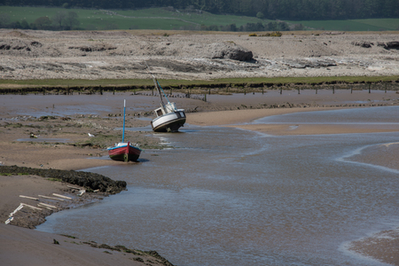 beached: A seascape of a harbor harbour at low tide with two small boats beached in the estuary Stock Photo