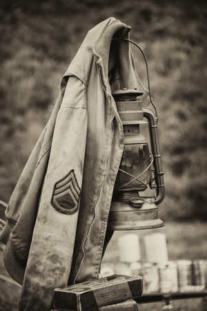 Sepia photograph of a US army sergeant jacket from WW2 hanging on a later in an upright vertical format Editorial