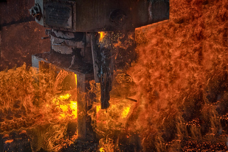 Close view of an industrial furnace being emptied with fire and flames predominant