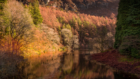 An autumn landscape shpwing the river Elan in the Elan valley mid Wales UK meandering between beautiful autumnal colours which are reflected in the river