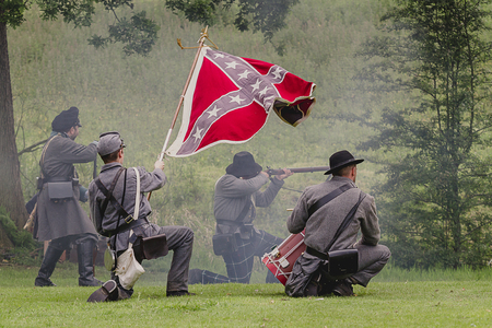 A group of four confederate soldiers firing weapon with a southern flag at a reenactment