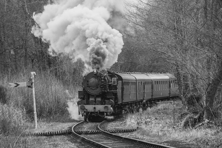 A black and white mono photograph of a vintage steam locomotive smoking heavily and coming forward