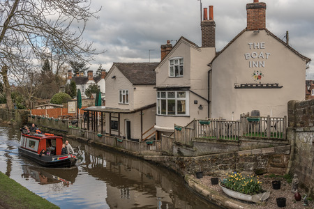 Gnosall, Staffordshire, UK - April 1 2018 - A canal boat with people enjoy a trip in a narrowboat passing a canal side pub  inn with reflections in the water
