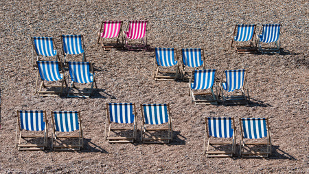 Deckchairs lined up on a pebble beach at the seaside. There are no people in the photograph. Two of the striped chairs are a different colour Stock fotó