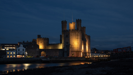 Caernarfon Castle, often anglicized as Carnarvon Castle, is a medieval fortress in Caernarfon, Gwynedd, north-west Wales. Taken here lit up at night Stock fotó