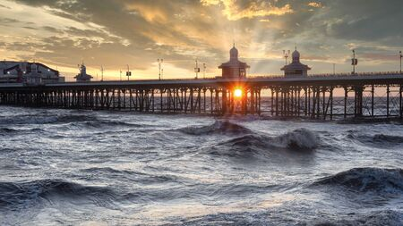The sun setting under the pier with sun rays. The photograph shows Blackpool north pier and a rough sea 免版税图像