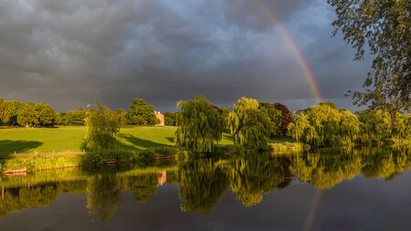 Wedgwood pools and Barlaston Hall. A landscape view with sunlight, stormy sky and rainbow reflected in the water