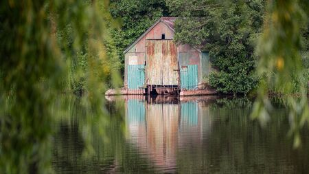 An old corrugated tin disused boathouse surrounded by trees standing at the edge of water and reflected on the surface