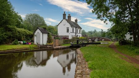 a lock keepers cottage is reflected in the still waters of the canal
