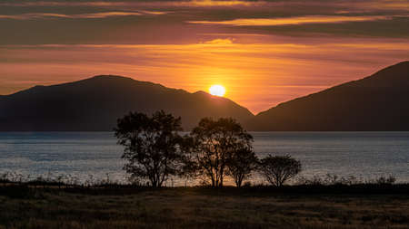 The sun setting behind the hills across Loch Linnhe in Scotland