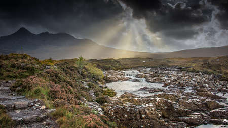 A stormy sky with sun beams over the river Sligachan on the Isle of Skye in Scotland