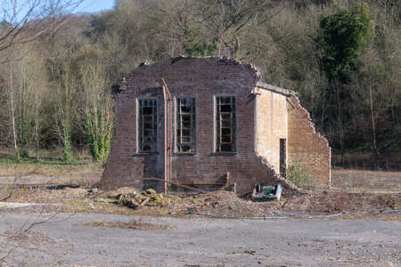 the remains of an old building. Most has already been demolished and the remains has broken windows and loose brickwork. There is no people in the photo and it is sunshine with a clear blue sky