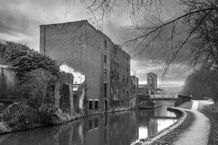 A black and white photograph showing urban decay. An old neglected building abandoned by the side of a canal