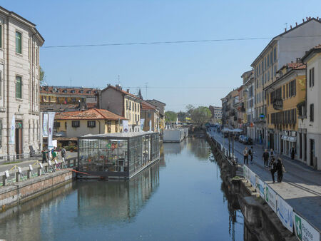 waterway: MILAN, ITALY - APRIL 09, 2014: Tourists visiting the Naviglio Grande canal waterway in Milan Italy
