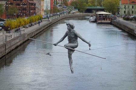 old port: BYDGOSZCZ, POLAND - CIRCA APRIL 2016: Przechodzacy przez rzeke (meaning Passing across the river) work of art by sculptor Jerzy Kedziora over River Brda in the old port