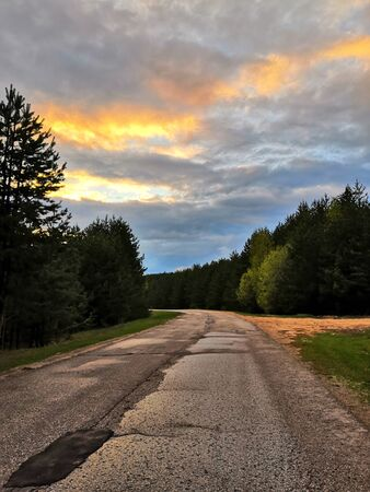 Beautiful landscape of sunset on the sky with clouds. Pine trees along the road. Asphalt road running along the edge of the coniferous forest through the valley to meet the mountain ranges. Russia. Фото со стока