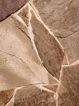 Background in the form of a stone wall made of many flat buta stones of light brown color. Brown stone fence