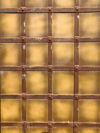 Metall wall fence gray yellow brown square background abstract texture. Фото со стока