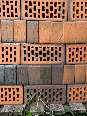 Close up red and orange bricks with round holes on a warehouse, Packed orange and red perforated bricks, Building material bricks, Red bricks stacked into cube, Storage brickwork product
