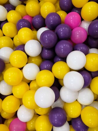 Colored plastic balls background. Violet yellow white pink plastic balls in pool of game room. Swimming pool for fun and jumping in colored plastic balls Фото со стока