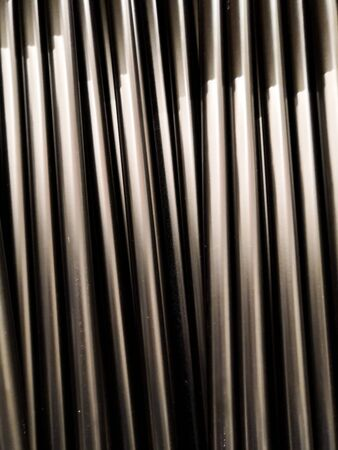 Aluminum pipes. Texture of metal pipes of the same diameter. The vertical arrangement of the elements.