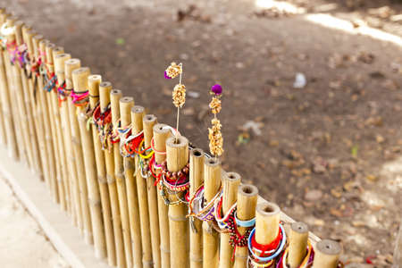 wristbands: Flowers on a bamboo fence at a mass grave in Cambodia