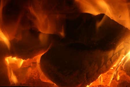 Hot coals inside a fireplace.