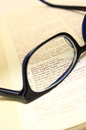 Bible open to the lords prayer with a pair of glasses on the pages. Stock Photo