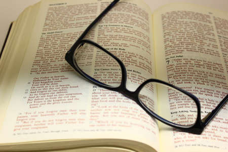 hallowed: Bible open to the lords prayer with a pair of glasses on the pages. Stock Photo