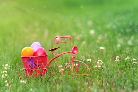 Colorful easter eggs in the basket of a pink tricycle in the grass.