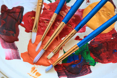 Artist paint brushes displayed on a plate of colorful dried paint