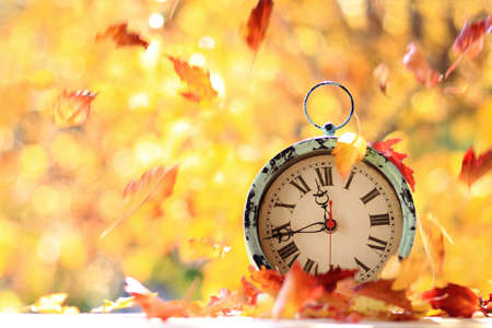 Autumn leaves blowing in the wind across an antique alarm clock 版權商用圖片