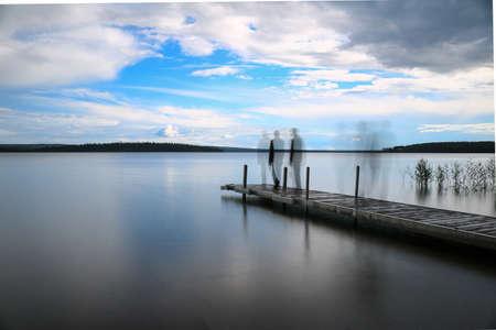湖の桟橋の上を歩く人のシルエット