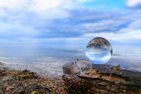 Transparent glass ball on a log reflecting calm blue water of a lake