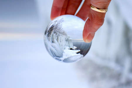 Transparent glass ball reflecting a frozen winter scene of a lake