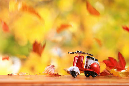 Autumn scence of a scooter surounded by falling leaves Standard-Bild - 110271503