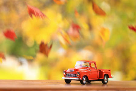 Autumn scence of an old truck surounded by falling leaves Standard-Bild - 110271504