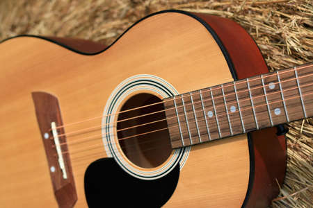 Close up of an acoustic guitar laying against a bail of hay Standard-Bild - 112617126