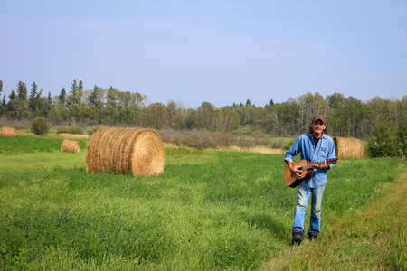 Handsome man with a and acoustic guitar in the field Standard-Bild - 112908512