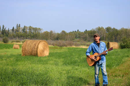 Handsome man with a and acoustic guitar in the field Standard-Bild - 112650294