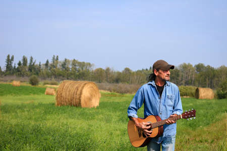 Handsome man with a and acoustic guitar in the field Standard-Bild - 112650296