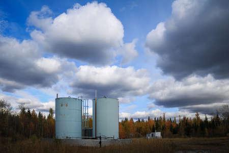 Blue bitumen tanks in a field under a clouded sky Standard-Bild - 117299826