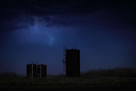 Bitumen tanks under a dark stormy sky Standard-Bild - 117299862