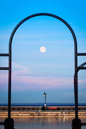 Sunset scene of the moon over the marina dock at Cold Lake, Alberta Standard-Bild - 117300011